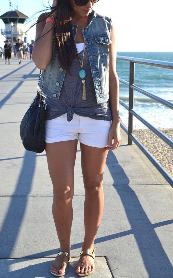 shorts blancos, una camiseta blanca, un top gris y un chaleco de mezclilla