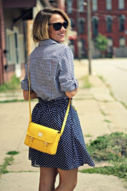 aspecto elegante con falda de lunares, camisa a cuadros y llamativo bolsa