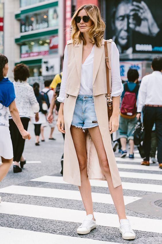 chaleco largo de color beige, pantalones cortos de mezclilla y una camisa blanca