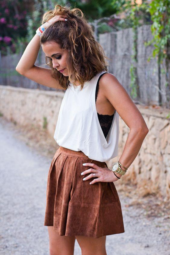 top de encaje negro, un top blanco en él y una falda de cuero de imitación de color marrón