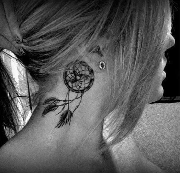 Tatuaje delicado atrapasueños detrás de la oreja.