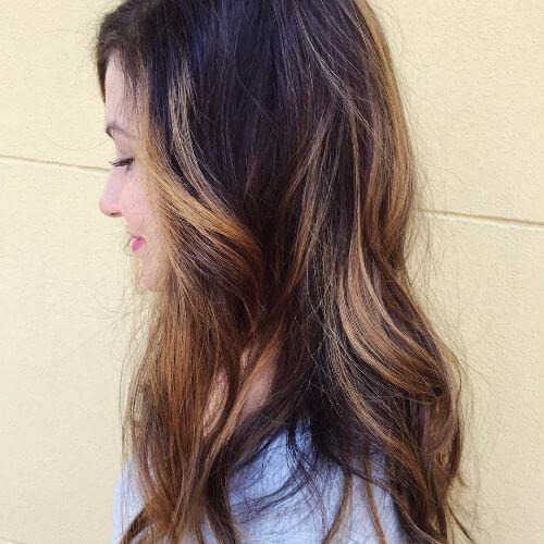cabello castaño ondulado con reflejos caramelo