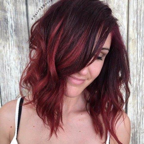 Puntos culminantes rojos en el pelo oscuro