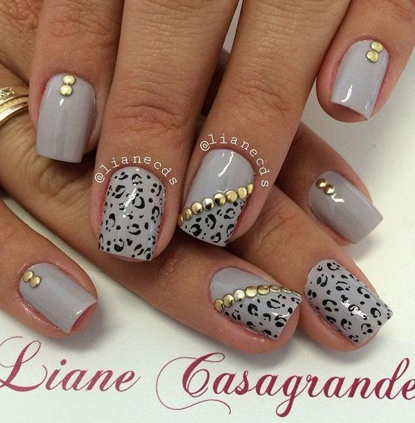 Uñas grises con estampados de leopardo y adornos dorados. Pinta sobre estampados de leopardo en tu esmalte de uñas gris y agrega adornos dorados en la parte superior para darle más acento.