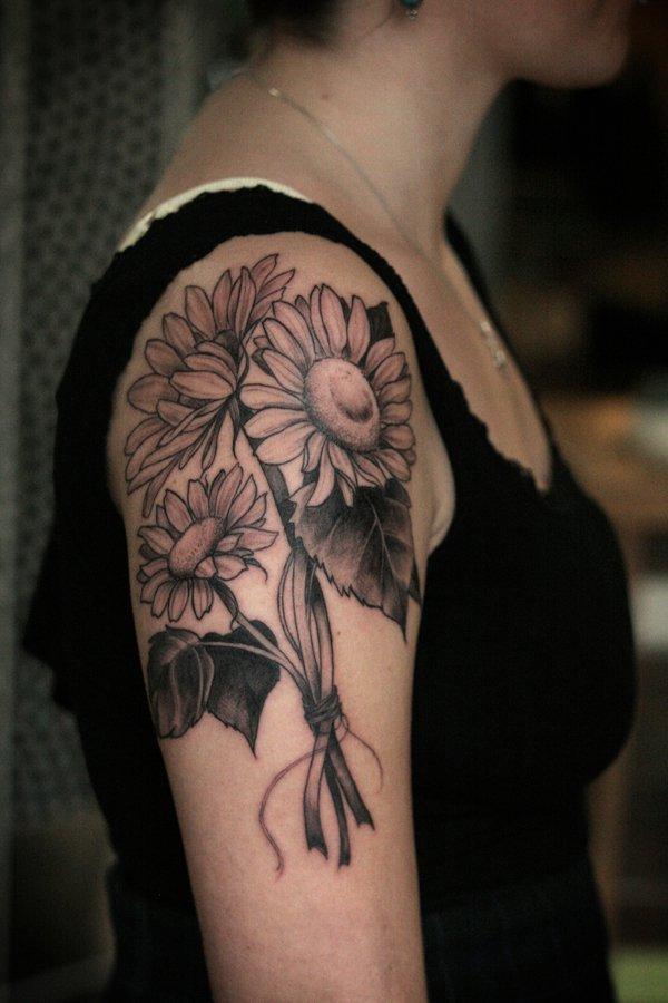 Diseño del tatuaje del brazo superior con un ramo de girasoles.