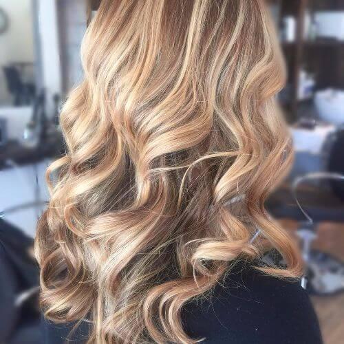 reflejos rubios sucios del balayage en el pelo largo y ondulado