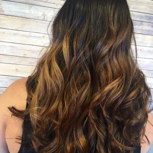 balayage caramelo en el pelo largo y grueso ondulado