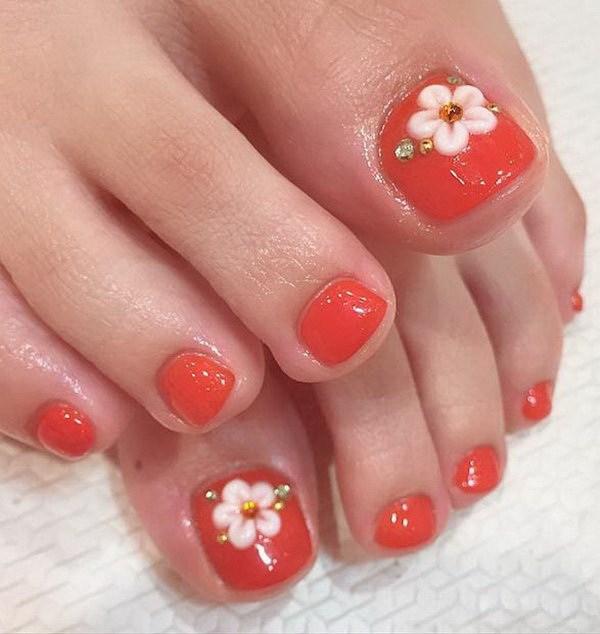 Diseño de uñas con toques acentuados de flores y rinones.