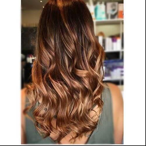 cabello castaño largo ondulado con reflejos caramelo