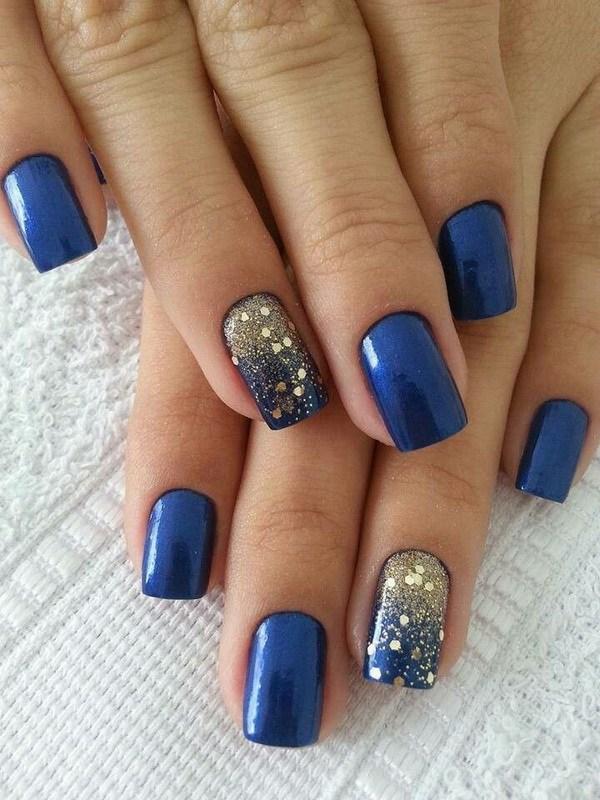 Diseño de uñas azul marino con lentejuelas doradas para acento.