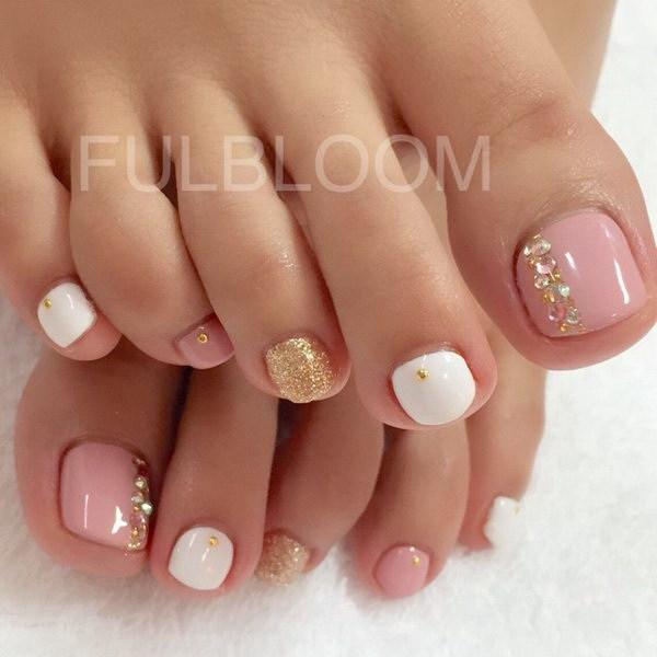 Pedicura rosa y blanco con brillo y gemas.