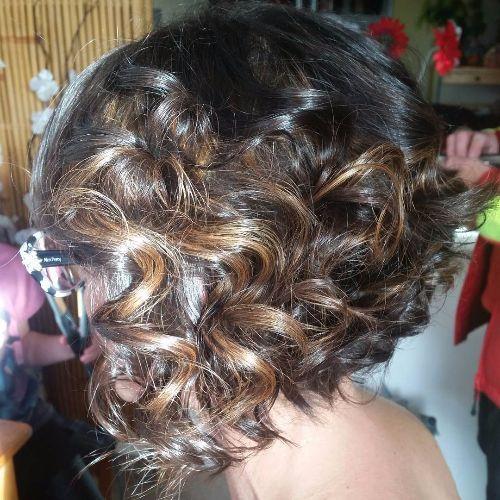 reflejos de caramelo rizado en el cabello oscuro