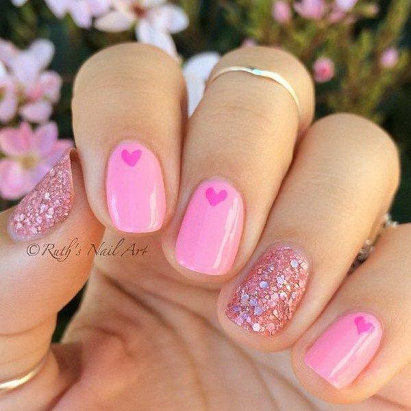 Uñas rosadas con corazones y lentejuelas.