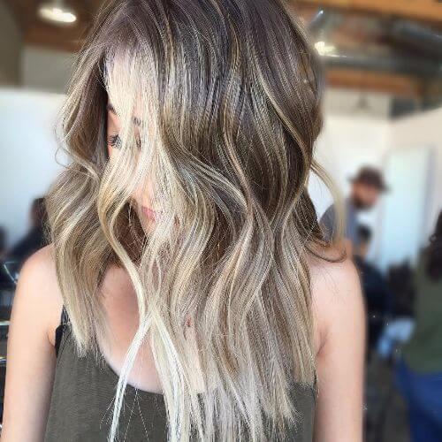capas entrecortadas en el pelo largo con reflejos rubios y caramelo