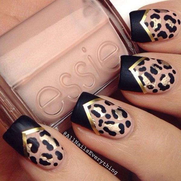 Diseño de uñas con estampado de leopardo con cinta dorada y puntas de chevron negras.