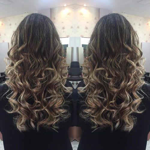 reflejos rubios en el pelo castaño largo y rizado