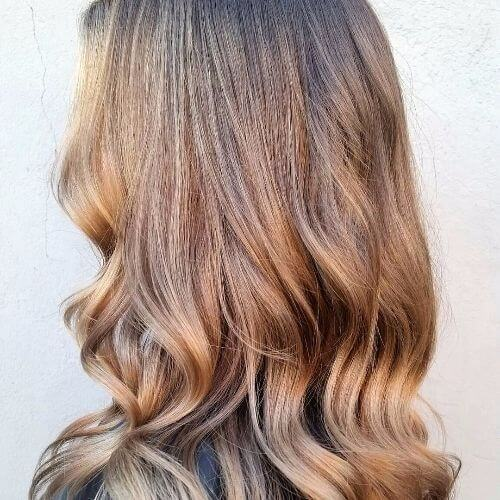 pelo largo de color marrón ceniza con reflejos de caramelo balayage