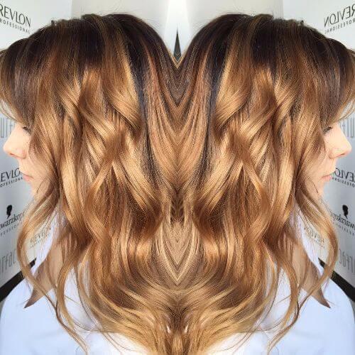 balayage caramelo en el pelo largo ondulado