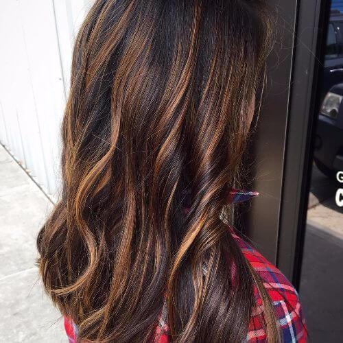 reflejos de caramelo en el pelo largo y ondulado