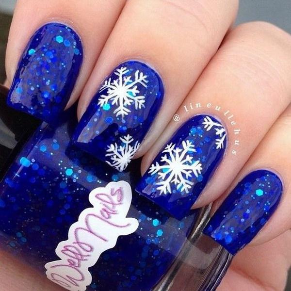 Diseño de los copos de nieve en uñas azules del brillo.