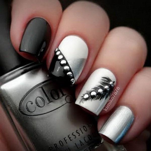 Uñas de plumas blancas y negras con pernos de plata.