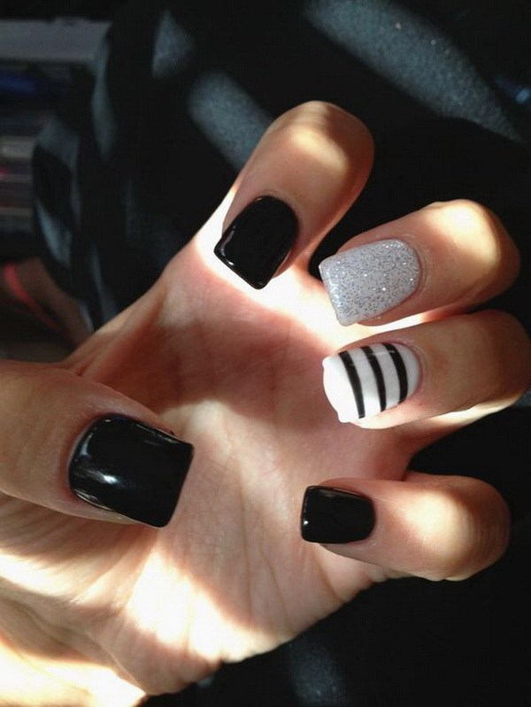 Uñas blancas y negras con brillo y rayas.