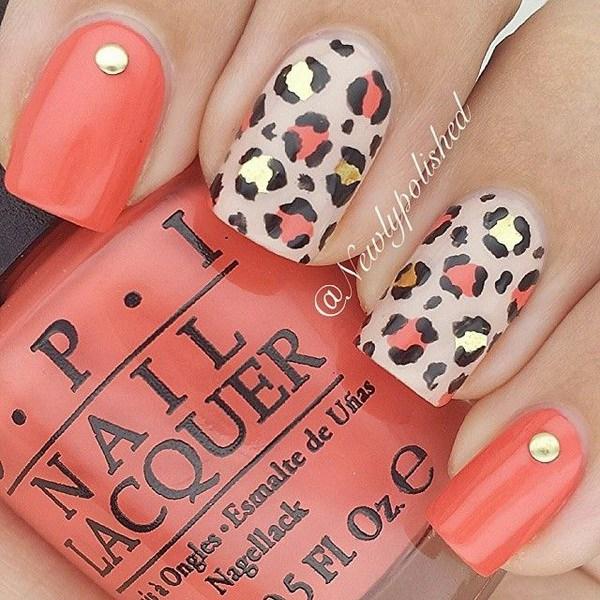 Leopardo o guepardo clavos con clavos.  Este diseño de uñas utiliza barniz de color coral y desnudo como revestimiento de base y agrega algunas impresiones de oro, negro y coral en la parte superior.