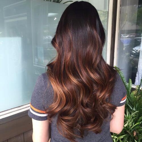 reflejos de caramelo en el cabello largo castaño oscuro