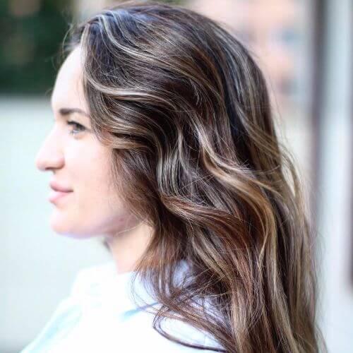 cabello oscuro con reflejos de caramelo en peinado ondulado