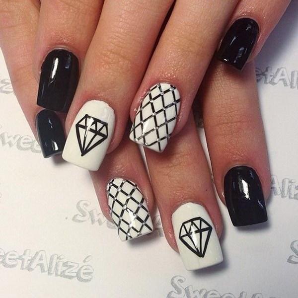 Diseño de uñas en blanco y negro con diamantes.