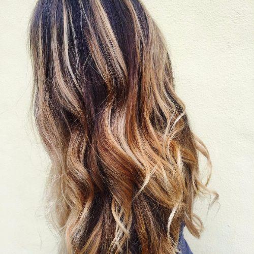 pelo largo y ondulado con reflejos de caramelo balayage