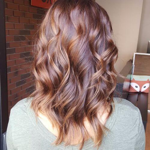 reflejos de caramelo en el pelo rojo ondulado