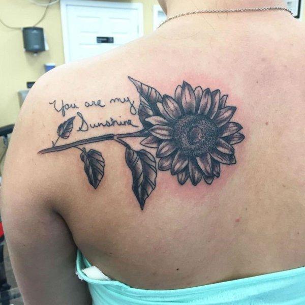 Tatuaje de girasol negro en el hombro. ¡Se ve increíble!